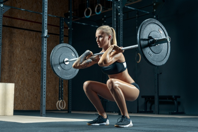 Muscular young woman lifting heavy weights